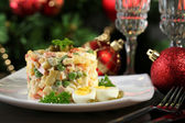 Russian traditional salad Olivier, on wooden table, on bright background — Stock Photo