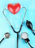 Tonometer, estetoscópio e coração em close-up de madeira mesa — Foto Stock