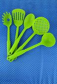 Plastic kitchen utensils on fabric background — Stock Photo