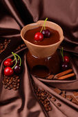 Chocolate fondue with fruits, on brown background — Stock Photo
