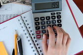 Woman hand counting on calculator on worktable background — Stock Photo