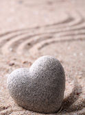 Grey zen stone in shape of heart, on sand background — Stock Photo