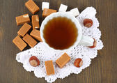Many toffee and cup of tea on napkin on wooden table — Stock Photo