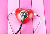 Estetoscopio y corazón en primer plano de la mesa de madera — Foto de Stock