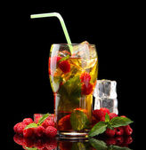 Iced tea with raspberries and mint on black background — Stock Photo