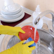 Close up hands of woman washing dishes in kitchen — Stock Photo #35000009