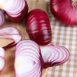 Stock Photo: Fresh red onions on cutting board close up