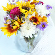 Bouquet of wild flowers in glass vase on light background — Stock Photo #35001691