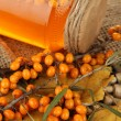 Branches of sea buckthorn with jam on wicker stand close up — Stock Photo