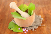 Ginkgo biloba leaves in mortar and pills on wooden background — Stock Photo