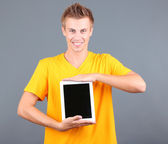 A handsome young man with tablet on grey background — Stock Photo