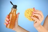 Female hand with wisp and bottle of shower gel, on color background — Stock Photo