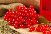 Red berries of viburnum on stand with cup of tea on table on sackcloth background — Stock Photo
