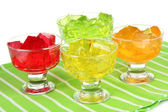 Tasty jelly cubes in bowls on table on white background — Stock Photo