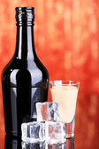 Baileys liqueur in bottle and glass on red background — Stock Photo