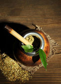 Calabash and bombilla with yerba mate on grey wooden background — Stock Photo