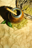Calabash and bombilla with yerba mate on old paper background — Stock Photo