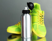 Sports bottle and sneakers on grey background — Stock Photo