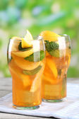 Iced tea with lemon and mint on wooden table, outdoors — Stock Photo