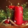 Two candles and christmas decorations, on brown background — Stock Photo #35015315