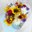 Bouquet of wild flowers in glass vase on light background — Stock Photo #35016197