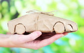 Woman hand holding a car wrapped in brown kraft paper, on nature background — Stock Photo