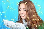 Vackra leende flicka med snö på blå bakgrund — Stockfoto