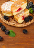 Tasty donuts with berries on wooden table — Stock Photo