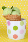 Appetizing green ice cream with waffle cone in cup on polka dot background — Stock Photo