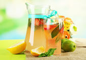 Basil lemonade with strawberry in jug and glass, on wooden table, on bright background — Stock Photo