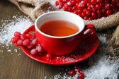 Kartopu çay kupası, çilek ve karda ahşap zemin üzerinde çul peçete ile natürmort — Stok fotoğraf
