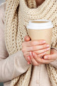 Hot drink in paper cup in hands close up — Stock Photo