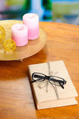 Composition with old book, eye glasses, candles, flowers on bright background — Stock Photo