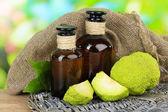 Osage Orange fruits (Maclura pomifera) and medicine bottles, on wooden table, on nature background — Stock Photo