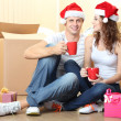 Young couple with boxes in new home celebrating New Years — Stock Photo #35025827