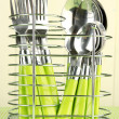 Knives, forks and spoons in metal stand on tablecloth on beige background — Stock Photo
