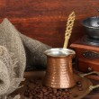 Coffee grinder, turk and coffee beans on golden tray on wooden background — Stock Photo #35026667