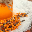 Branches of sea buckthorn with jam and snow on wooden background — Stock Photo