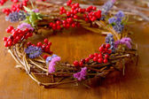 Wreath of dry branches with flowers and viburnum on wooden table close-up — 图库照片