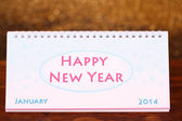 New Year calendar on wooden table, on shiny golden background — Stock Photo