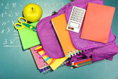 Purple backpack with school supplies — Stock Photo