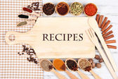 Various spices and herbs with empty wooden board — Stock Photo