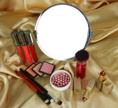 Round table mirror with cosmetics on fabric background — Stock Photo