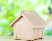 House wrapped in brown kraft paper, on nature background — Stock Photo