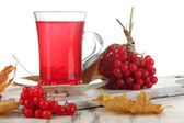 Red berries of viburnum and cup of tea on table on white background — Stock Photo