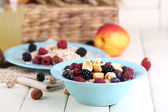 Oatmeal in plates with berries on napkins on wooden table on bright background — Stock Photo