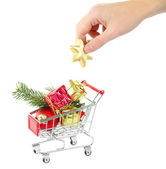 Hand and Christmas gifts in shopping trolley — Stock Photo