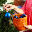 Decorating Christmas tree on bright background — Stock Photo #35077837