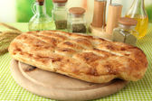 Pita bread on wooden stand with spices on tablecloth on bright background — Stock Photo