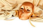 Mask on gold fabric on white background — Stock Photo